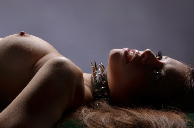 A woman with spiked collar, bare breasted, laying on her back
